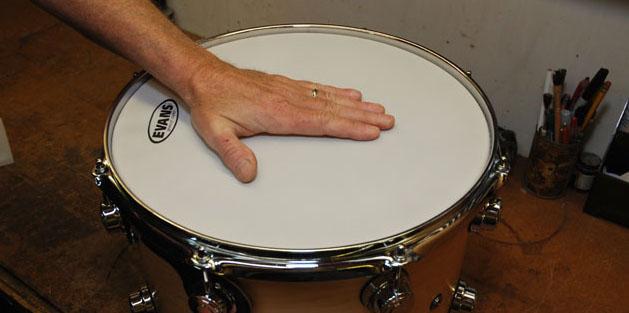applying hands pressure on the drum