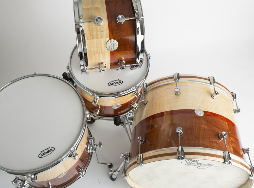 """Doc Sweeney showed its Dual Species kit (22"""" x 15"""", 16"""" x 15"""", 13"""" x 9"""", and 12"""" x 8"""") at Winter NAMM 2017. The shells, which are .25"""" thick with milled reinforcing rings, feature a hand rubbed oil finish and combine Tiger Maple and figured Makore with Redheart band."""