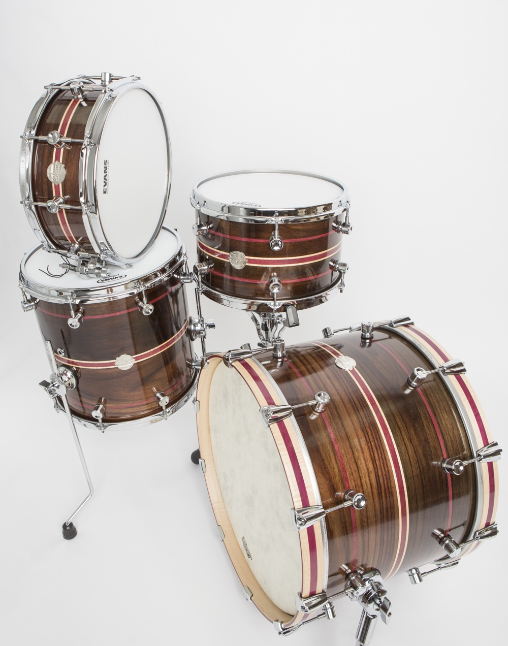 """Doc Sweeney's Panther Kit inlay (comprising a 20"""" x 14"""" bass drum; 14"""" x 14"""" and 13"""" x 8"""" mounted toms; and 14"""" x 5.5"""" snare drum) is made of steam-bent East Indian rosewood with purpleheart and maple inlays. It also features curly maple hoops with purpleheart. Have you ever seen another complete kit made of solid rosewood?"""